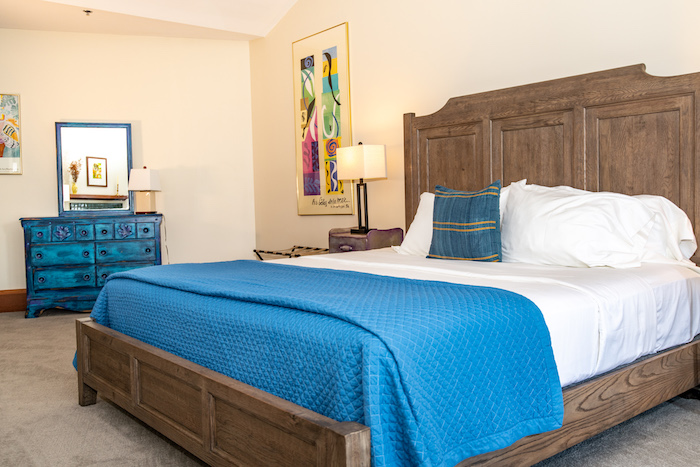 King bed with blue comforter and dresser